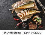 Stock photo appetizing smoked fish with spices cutlery pepper and bread on craft paper over dark stone 1344793370