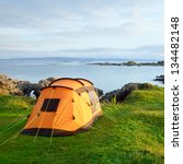 Camping tent on an ocean shore in a morning light - stock photo