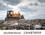 Small photo of bulldozer working on landfill with birds in the sky