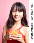 young asian woman drink orange... | Shutterstock . vector #1345024703