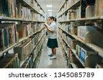 schoolgirl selecting book from... | Shutterstock . vector #1345085789