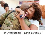 Millennial black soldier returning home to his family, embracing his mother, close up - stock photo