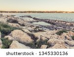 wild stony beach. blue sea  | Shutterstock . vector #1345330136
