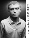 Portrait of a handsome blond teenager boy with cute flecks on his face posing over silver background. Black and white (monochrome) studio shot. - stock photo
