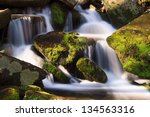 Water Falls Over A Jumble Of...