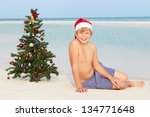 boy sitting on beach with... | Shutterstock . vector #134771648