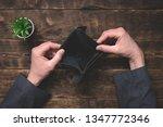 empty wallet in hands on an... | Shutterstock . vector #1347772346