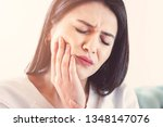 Small photo of Woman suffering from toothache, tooth decay or sensitivity.