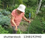 old woman working in a summer... | Shutterstock . vector #1348192940
