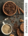 Small photo of Black fried coffee beans in cafe with cookie and cake on dark textured background