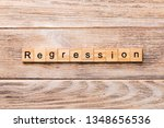 Small photo of regression word written on wood block. regression text on wooden table for your desing, concept.