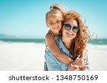 Small photo of Smiling mother and beautiful daughter having fun on the beach. Portrait of happy woman giving a piggyback ride to cute little girl with copy space. Portrait of kid embracing her mom during summer.
