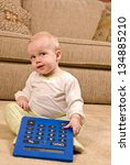 A young baby in a pair of generic pajamas sitting on the floor with a large, over-sized calculator. She appears to be looking up and camera right to the area left open for copy space. - stock photo