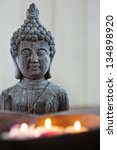 Buddha figure with floating candles in a stone bowl - stock photo