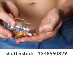 man taking pills  bottle with... | Shutterstock . vector #1348990829