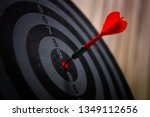 Stock photo close up shot of the dart arrow hit on bulleyes of dartboard to represent that the business reached 1349112656