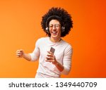 Bushy millennial black guy singing into smartphone like microphone and listening to music via wireless earphones, orange background