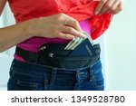 Small photo of Woman getting cash and passport from hidden travel money belt she has under her clothes to protect herself from pickpocket thieves and credit card scanners safely transporting documents in transit.