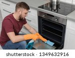young man cleaning oven with... | Shutterstock . vector #1349632916