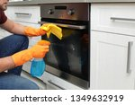 young man cleaning oven with... | Shutterstock . vector #1349632919