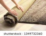 Woman Rolling Carpet On Floor...