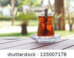 Glass with hot turkish tea on a sunny terrace - stock photo