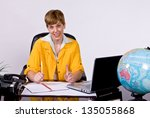Female sitting behind a desk in bright, yellow jacket working on a laptop computer. - stock photo