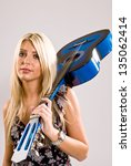 A beautiful young, blonde, female holding a blue guitar over her shoulder in a floral print dress and a look of attitude on her face. - stock photo