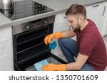 young man cleaning oven with... | Shutterstock . vector #1350701609