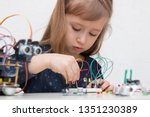 Small photo of A cute girl constructs metal robot and program it. The boards and microcontrollers are on the table. STEM education inscription. Programming. Mathematics. The science. Technologie. DIY.