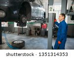 mechanic with wrench looks at... | Shutterstock . vector #1351314353