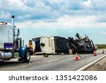 Fifth wheel RV overturned on highway with wench truck trying to get it off the road and two semis parked nearby and traffic cones keeping traffic away - stock photo