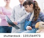 Friendly doctor showing an x-ray image of a broken bone to a young patient, the girl is wearing an arm brace - stock photo