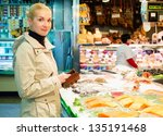 Young Blond Woman Buying Fish...