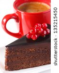 Piece of chocolate cake with berry and cup of coffee. - stock photo