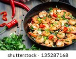 Freshly fried shrimps with herbs on old pan - stock photo