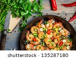 Shrimps fried on pan with fresh herbs - stock photo