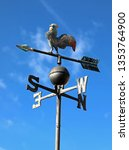 Small photo of old vintage weathercock in iron on blue sky background