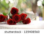 red roses on table in overwrap | Shutterstock . vector #135408560