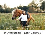 the girl standing near a horse... | Shutterstock . vector #1354255913