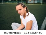 girl sits on the football field | Shutterstock . vector #1354265450