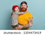 Small photo of Isolated shot of happy father with ginger beard, yellow t shirt, carries small daughter, recieves hug with love, spend free time together in family circle, express positive emotions. Parents, children