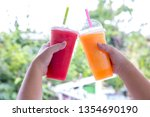 fruit smoothie. hand holding... | Shutterstock . vector #1354690190