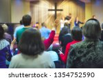 Small photo of Christian congregation worship God together, with cross with light rays in background