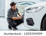 asian mechanic cleaning the car ... | Shutterstock . vector #1355294909