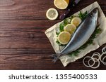 Stock photo delicious salted herring fish lies on paper with lemon slices onion rings parsley dill salted 1355400533
