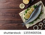Stock photo salted herring fish lies on paper with lemon slices onion rings parsley dill salted herring 1355400536