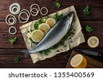 Stock photo salted herring lies on paper with lemon slices onion rings parsley dill salted herring lies on 1355400569