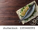 Stock photo herring lies on paper with lemon slices onion rings parsley dill salted herring lies on a brown 1355400593