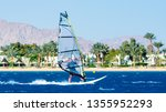 windsurfer rides on the waves... | Shutterstock . vector #1355952293